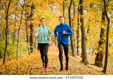 Young couple jogging together in beautiful autumn nature - stock photo
