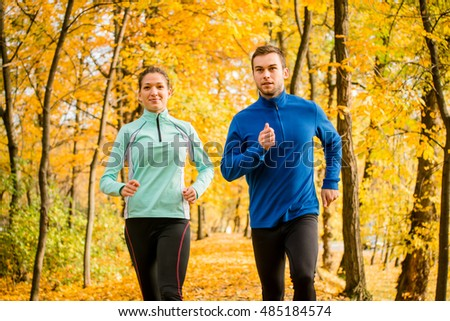 Young couple jogging together in beautiful autumn nature