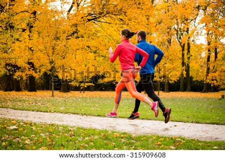 Young couple jogging together in park - autumn season - stock photo