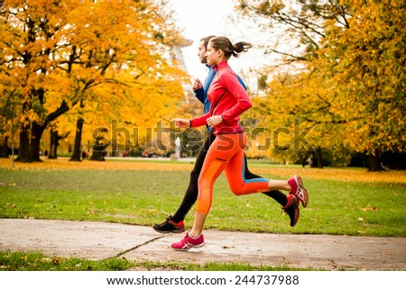 Young couple jogging together in park - rear view - stock photo