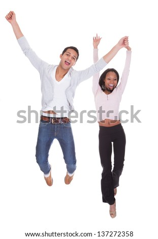 Young Couple Jumping In The Air Over White Background - stock photo