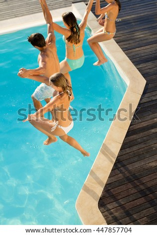 young couple jumping into swimming pool - stock photo