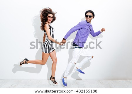 Young couple jumping isolated on a white background - stock photo