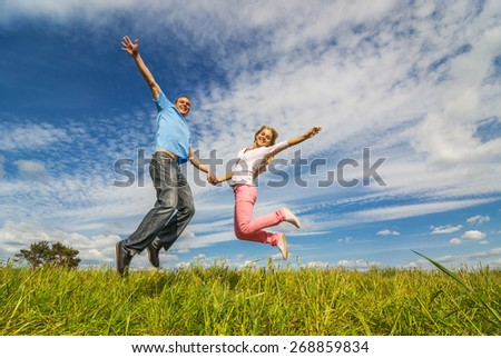 Young couple jumping on background of blue sky. - stock photo