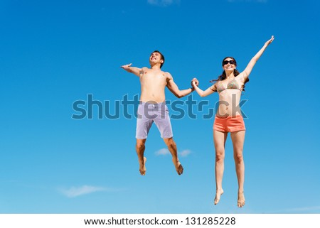 young couple jumping together on a blue sky background