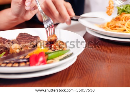 Young couple (just hands to be seen) enjoying dinner, he has some noodles while she is eating a good steak - stock photo