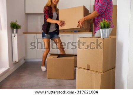 Young couple just move to their new apartment. They are unpacking stuff - stock photo