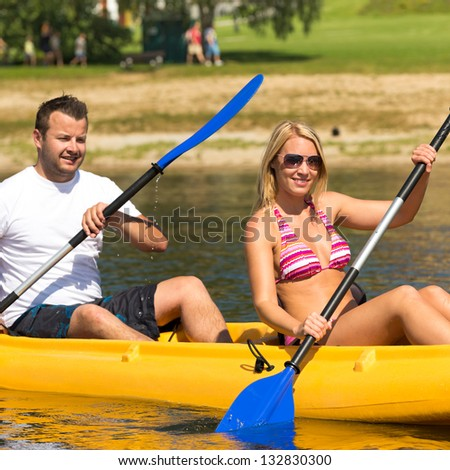 Young couple kayaking summertime in the sunshine vacation - stock photo
