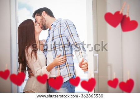 Young couple kiss as they open front door against hearts hanging on a line - stock photo