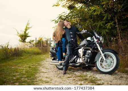 Young couple kiss in mirror on beautiful bike on road. - stock photo