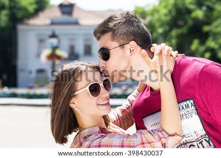young couple kiss street outdoor in summer