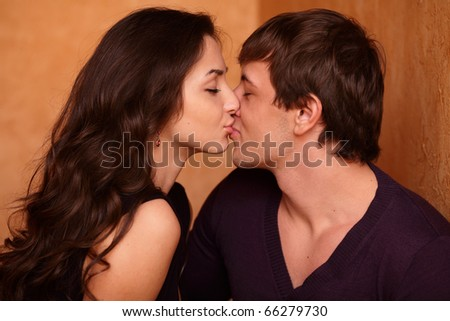 Young couple kissing at home - stock photo