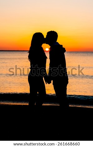 Young couple kissing at sunrise - stock photo