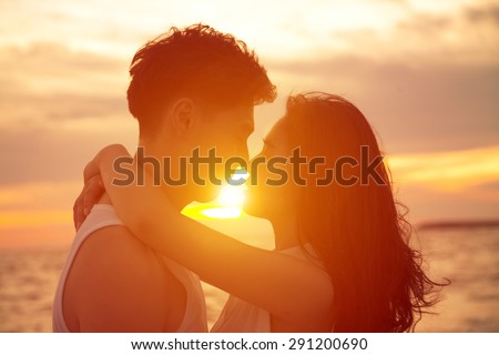 young couple  kissing at sunset on beach - stock photo