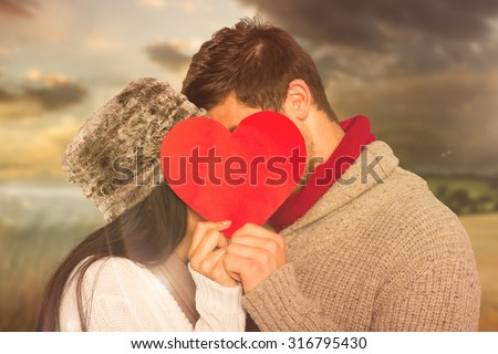 Young couple kissing behind red heart against country scene - stock photo