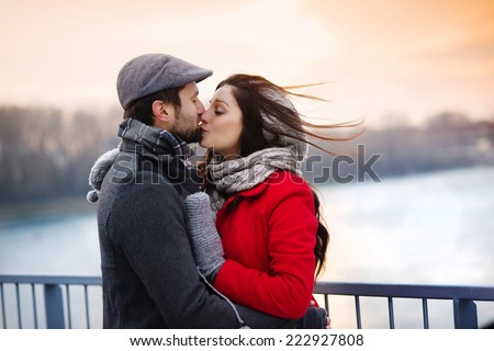 Young couple kissing by the river in winter weather - stock photo