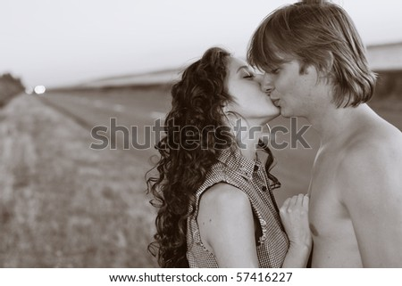 Young couple kissing each other at the edge of a nice road near the sea.