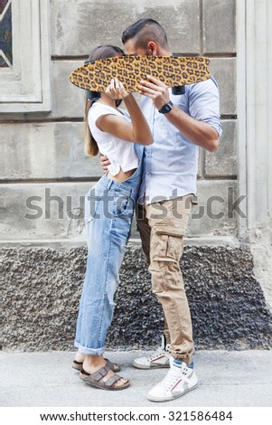 young couple kissing hiding behind a skateboard - stock photo