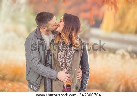 Young couple kissing in a park - stock photo