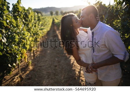 young couple kissing in a vineyard.