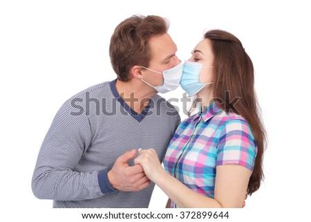 young couple kissing in medical masks - stock photo