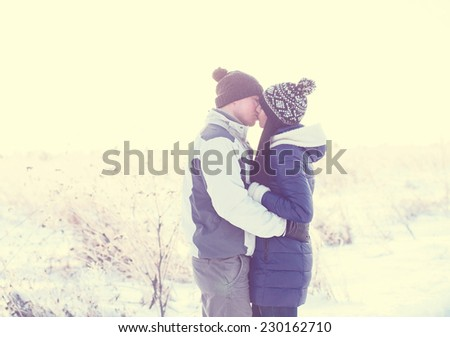 Young couple kissing in nature in winter - stock photo