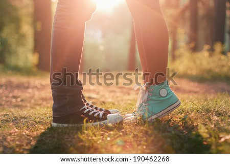 Young couple kissing in summer sun light. Kiss love standing - stock photo