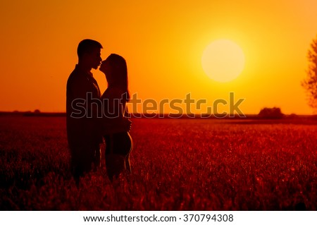 Young couple kissing in the field of wheat on sunny summer day.
