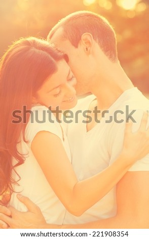Young couple kissing in the park. - stock photo