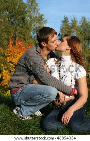 Young couple kissing in the park - stock photo