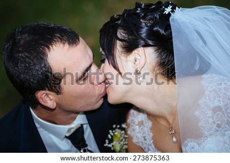 Young couple kissing in wedding gown. Bride holding bouquet of flowers.