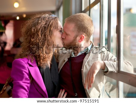Young couple kissing near the window inside the building.