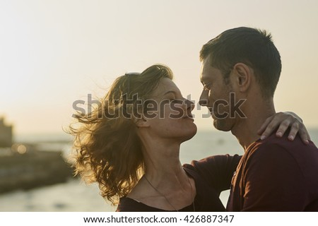 Young couple kissing on a sunset.