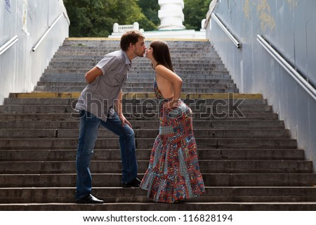 Young couple kissing on stairs in a tunnel - stock photo