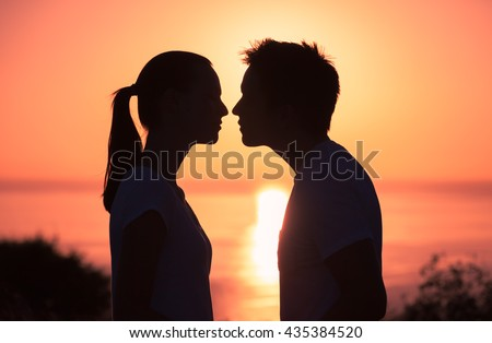 Young couple kissing on the beach during sunset.  - stock photo