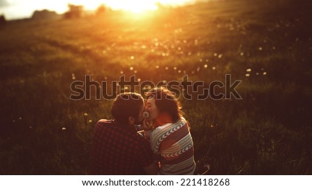 young couple kissing on the field of dandelions - stock photo