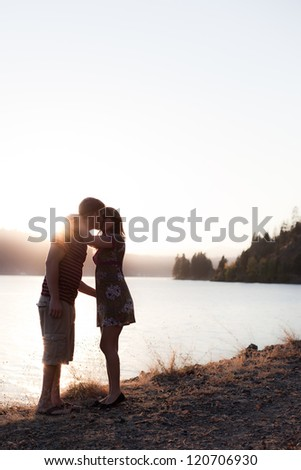 young couple kissing on the shore with the sun behind them, dramatic and low color - stock photo