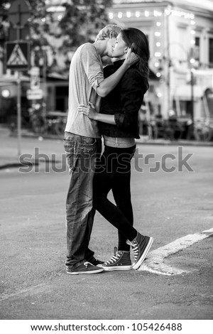 Young couple kissing on the street. Photo in black and white style.