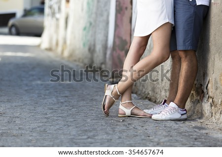 Young couple kissing outdoor. Male and female legs