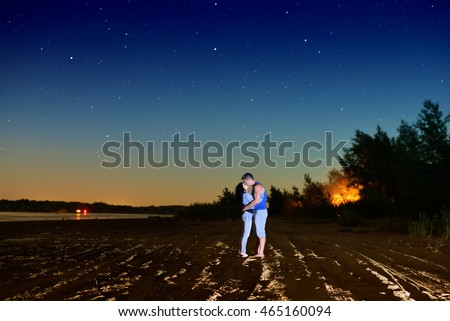 Young couple kissing under the stars on the beach at night