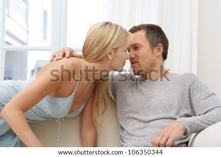 Young couple kissing while lounging on a white sofa at home. - stock photo