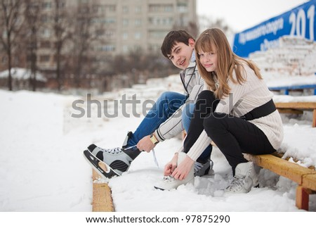 Young couple lacing up the skates - stock photo