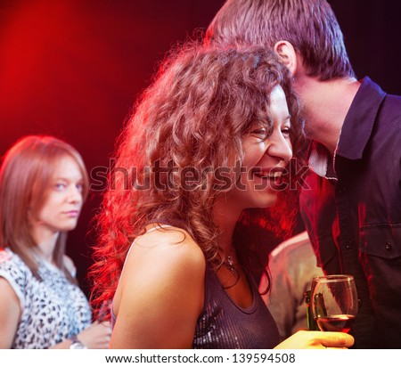 Young couple laughing and whispering while Woman in the backround is looking at them jealously, in night club, focus on couple. - stock photo