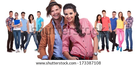 young couple laughing in front of a large group of casual friends on white background - stock photo