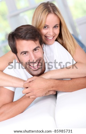 Young couple laying down sofa