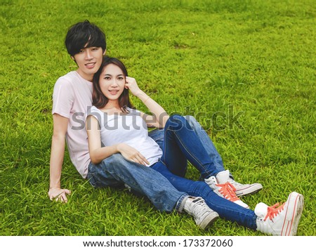 young couple laying on park  - stock photo