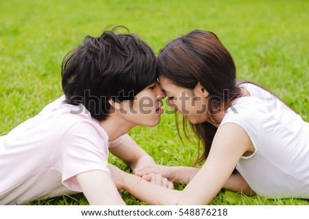 young couple laying on park lawn