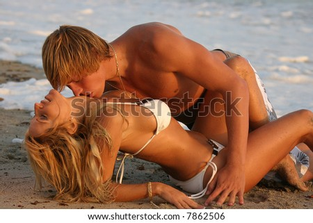 Young Couple laying on the Beach kissing at Sunset - stock photo