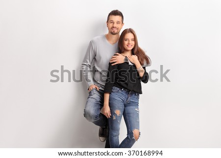Young couple leaning against a white wall and looking at the camera  - stock photo