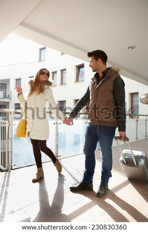 Young couple leaving apartment house with small luggage.